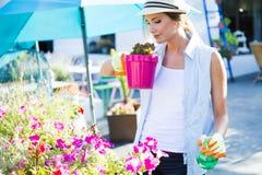 Piękna młoda kobieta bierze opiekę ogrodowy dom Obraz Stock