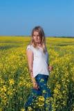 Piękna młoda kobieta, blondynek pozy w polu żółci kwiaty Obrazy Stock