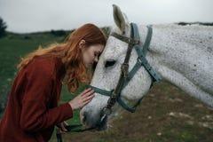 Piękna młoda kobieta chodzi w naturze z koniem w górach Zdjęcia Stock