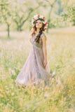 Piękna młoda kobieta chodzi w ogrodowy przyglądający up z wiankiem ren i biali kwiaty fotografia royalty free