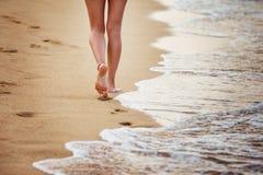 Piękna młoda kobieta chodzi wzdłuż seashore opuszcza odciski stopy Fotografia Royalty Free