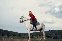 Piękna młoda kobieta chodzi z koniem na naturze w górach Zdjęcia Stock
