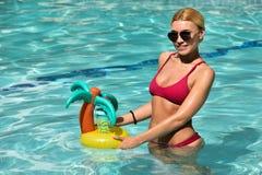 Piękna młoda kobieta cieszy się ciepłego słonecznego dzień w pływackim basenie Zdjęcie Royalty Free