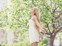 Piękna młoda kobieta cieszy się odór w kwieceniu zdjęcia stock