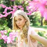 Piękna młoda kobieta cieszy się słonecznego dzień w parku podczas czereśniowego okwitnięcia sezonu na ładnym wiosna dniu obraz royalty free