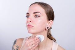 Piękna młoda kobieta czyści jej szyję z bawełnianą gąbką Zdjęcie Stock