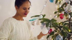 Piękna młoda kobieta dekoruje choinki dla świętowania boże narodzenia zdjęcie wideo