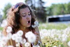 Piękna młoda kobieta dmucha dandelion Zdjęcie Royalty Free