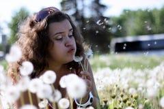 Piękna młoda kobieta dmucha dandelion Zdjęcie Stock