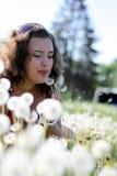 Piękna młoda kobieta dmucha dandelion Zdjęcia Royalty Free