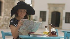 Piękna młoda kobieta dostać przegraną w miejscowości wypoczynkowej sprawdza mapę, patrzejący wprawiać w zakłopotanie, zbiory
