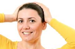 Piękna młoda kobieta dotyka jej włosy odizolowywającego na w z rękami Obrazy Stock