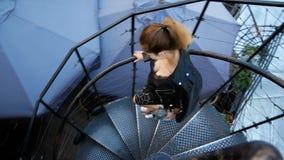 Piękna młoda kobieta iść puszek ślimakowaty schody i śliczny patrzeje up Kobiecy neckline jest odgórnym widokiem zbiory
