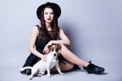 Piękna młoda kobieta i jej psi obsiadanie przed cudownym Zdjęcia Royalty Free