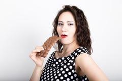 Piękna młoda kobieta je czekoladowego baru, jest ubranym suknię z polek kropkami wyraża różne emocje Zdjęcie Stock