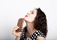 Piękna młoda kobieta je czekoladowego baru, jest ubranym suknię z polek kropkami wyraża różne emocje Zdjęcia Stock