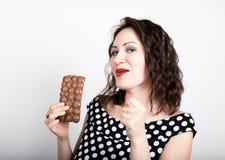 Piękna młoda kobieta je czekoladowego baru, jest ubranym suknię z polek kropkami wyraża różne emocje Obrazy Royalty Free