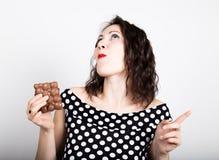 Piękna młoda kobieta je czekoladowego baru, jest ubranym suknię z polek kropkami wyraża różne emocje Fotografia Stock
