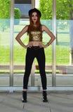 Piękna młoda kobieta jest ubranym czarnego kapelusz, złota odgórny i czarny cajgów modelować Dziewiętnaście ` s stylów Mody sesja Zdjęcie Stock