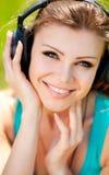 Piękna młoda kobieta jest ubranym hełmofony outdoors słucha muzyka Zdjęcie Royalty Free