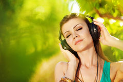 Piękna młoda kobieta jest ubranym hełmofony plenerowych słucha muzyka Zdjęcia Stock