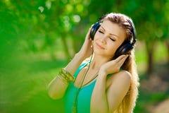 Piękna młoda kobieta jest ubranym hełmofony plenerowych słucha muzyka Obrazy Stock