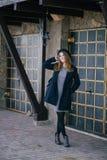 Piękna młoda kobieta jest ubranym kapelusz i błękitnego żakieta odprowadzenie na miasto ulicie Fotografia Royalty Free