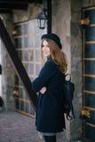 Piękna młoda kobieta jest ubranym kapelusz i błękitnego żakieta odprowadzenie na miasto ulicie Obrazy Royalty Free
