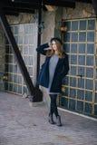 Piękna młoda kobieta jest ubranym kapelusz i błękitnego żakieta odprowadzenie na miasto ulicie Obraz Stock