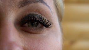 Piękna młoda kobieta jest ubranym subtelnego makeup mruga ona oczy, zamyka w górę widoku jej twarz zbiory