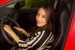 Piękna młoda kobieta jest ubranym wełny kurtkę i pozuje dla kamery w czerwonym samochodzie Fotografia Stock