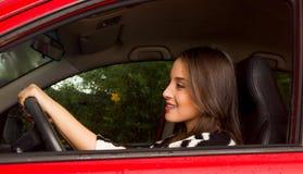 Piękna młoda kobieta jest ubranym wełny kurtkę i pozuje dla kamery w czerwonym samochodzie Obrazy Stock