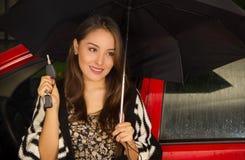 Piękna młoda kobieta jest ubranym wełny kurtkę i pozuje dla kamery w czerwonym samochodzie podczas gdy trzyma parasol z jeden Zdjęcia Stock