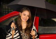 Piękna młoda kobieta jest ubranym wełny kurtkę i pozuje dla kamery w czerwonym samochodzie podczas gdy trzyma parasol z jeden Fotografia Stock