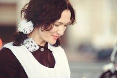 Piękna młoda kobieta, kędzierzawa fryzura i łęki w na wolnym powietrzu, Szczęśliwy i zdrowy ubierający w Radzieckim mundurku szko Obraz Royalty Free