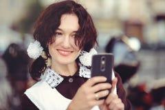 Piękna młoda kobieta, kędzierzawa fryzura i łęki w na wolnym powietrzu, Szczęśliwy i zdrowy ubierający w Radzieckim mundurku szko Obraz Stock
