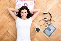 Piękna młoda kobieta kłaść na podłoga z elektronicznym gad, obraz royalty free