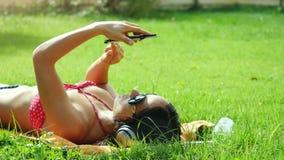 Piękna młoda kobieta kłama na trawie w okularach przeciwsłonecznych, słucha muzyka, używa telefon komórkowego i śpiewacką piosenk zbiory