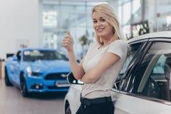 Piękna młoda kobieta kupuje nowego samochód przy przedstawicielstwem handlowym zdjęcia stock