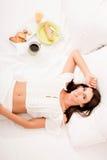 Piękna młoda kobieta ma śniadanie w łóżku zdjęcie royalty free