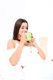 Piękna młoda kobieta ma jej pierwszy kawę w łóżku fotografia royalty free