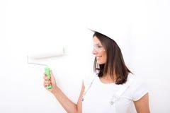 Piękna młoda kobieta maluje mieszkanie fotografia stock