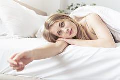 Piękna młoda kobieta na łóżku, 20s roczniak zdjęcie stock