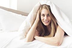 Piękna młoda kobieta na łóżku, 20s roczniak zdjęcia stock