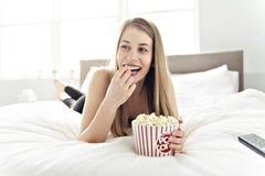 Piękna młoda kobieta na łóżku, 20s roczniak z popkornem zdjęcie stock
