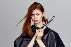 Piękna młoda kobieta na świetle - szary tło trzyma włosianego curry'ego dla jej włosy, fryzura Fotografia Royalty Free
