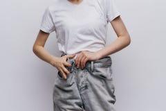 Piękna młoda kobieta na białym odosobnionym tle, dieta, ciężar strata, postęp, sukces Obraz Stock