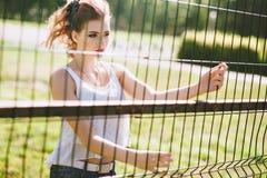 Piękna młoda kobieta na zielonym boisku piłkarskim Dziewczyny pozycja przy futbolową bramą, ubierającą w niebieskich dżinsach, bi Zdjęcia Stock