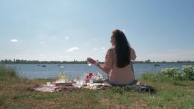 Piękna młoda kobieta napojów woda od szkła i cieszy się odpoczynek podczas gdy relaksujący na pinkinie na zielonym gazonie rzeką zbiory