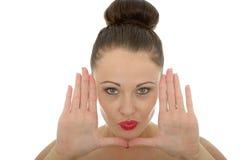 Piękna młoda kobieta Obramia Jej twarz Z Ona ręki Patrzeje brzęczenia obraz royalty free